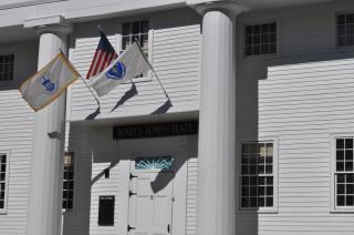 A photograph of the Old Town Hall doorway with U.S., State and Town flags flying above it.